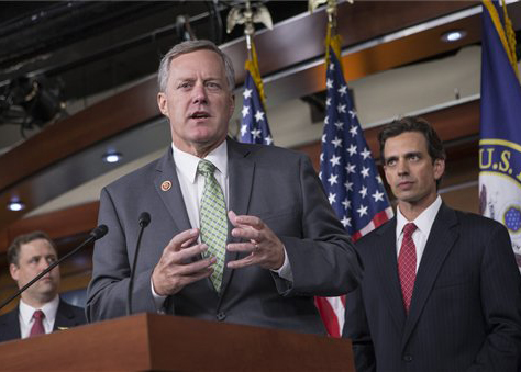 Rep. Mark Meadows, R-N.C, center, Rep. Tom Graves, R-Ga., right, and other conservative Republicans discuss their goal of obstructing the Affordable Care Act, popularly known as Obamacare, as part of a strategy to pass legislation to fund the government, on Capitol Hill in Washington, Thursday, Sept. 19, 2013.  Photo courtesy of the Associated Press