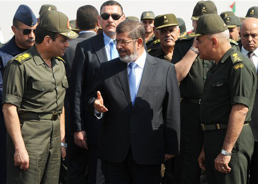 In this Wednesday, Oct. 10, 2012 file photo released by the Egyptian Presidency, then Egyptian President Mohammed Morsi, center, speaks with Minister of Defense, Lt. Gen. Abdel-Fattah el-Sissi, left, at a military base in Ismailia, Egypt. An Egyptian court has set Nov. 4, 2013, as the start date for the trial of ousted President Mohammed Morsi on charges of incitement to murder for the killings of opponents who were rallying outside his palace while he was in office. Morsi, ousted in a popularly-backed military coup in July, has been held incommunicado since.  (Photo Courtesy of the Associated Press and Egyptian Presidency)