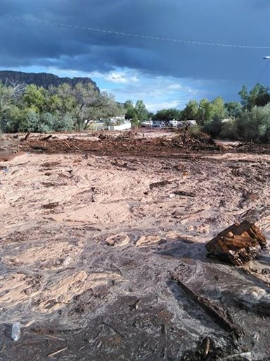 Debris and water cover the ground after a flash flood Monday, Sept. 14, 2015, in Hildale, Utah. Authorities say multiple people are dead and others missing after a flash flood ripped through the town on the Utah-Arizona border Monday night. (Mark Lamont via AP)