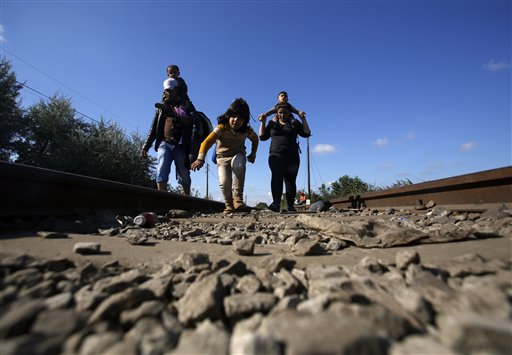 Migrants cross a border line between Serbia and Hungary near Roszke, southern Hungary, Tuesday, Sept. 8, 2015. Hungarian police stood by as thousands of migrants boarded cross-border trains Sunday into Austria, taking advantage of Hungary's surprise decision to stop screening international train travelers for travel visas, a get-tough measure that the country had launched only days before to block their path to asylum in Western Europe. (AP Photo/Darko Vojinovic)
