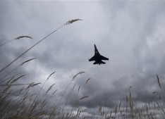 In this photo taken Thursday, Oct. 15, 2015 , a Sukhoi SU-27 jet of the aerobatics team Russian Knights approaches to land at Kubinka Air Base in Kubinka, 65 kilometers (40 miles) outside Moscow, Russia. In Kubinka, a vast workshop that upgrades warplanes of the kind Russia is using in Syria is the town's main lifeblood, and support for the Syria campaign is strong among the town residents. (AP Photo/Pavel Golovkin)