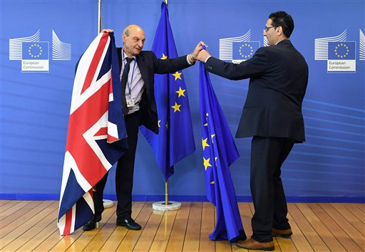 Members of protocol adjust the British and EU flags prior to the arrival of British Prime Minister David Cameron at EU headquarters in Brussels on Tuesday, June 28, 2016. EU heads of state and government meet Tuesday and Wednesday in Brussels for the first time since Britain voted to leave the European Union, throwing British and European politics into disarray. (AP Photo/Geert Vanden Wijngaert)