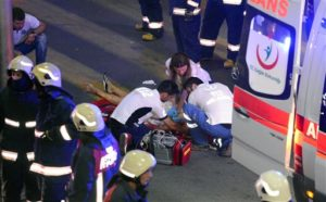 Turkish rescue services members help a wounded person outside Istanbul's Ataturk airport, Tuesday, June 28, 2016. Explosions rocked Istanbul's Ataturk airport, killing dozens of people and wounding scores of others, Turkey's justice minister and another official said Tuesday. (Ismail Coskun/IHA via AP) TURKEY OUT