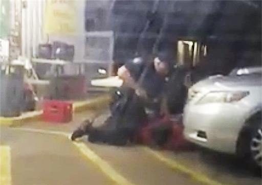 In this Tuesday, July 5, 2016 photo made from video, Alton Sterling is held by two Baton Rouge police officers, with one holding a hand gun, outside a convenience store in Baton Rouge, La. Moments later, one of the officers shot and killed Sterling, a black man who had been selling CDs outside the store, while he was on the ground.  Photo by Arthur Reed, AP.