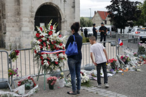 People gather to pay respect with flowers and candles next to the church where an hostage taking left a priest dead the day before in Saint-Etienne-du-Rouvray, Normandy, France, Wednesday, July 27, 2016. The Islamic State group crossed a new threshold Tuesday in its war against the West, as two of its followers targeted a church in Normandy, slitting the throat of an elderly priest celebrating Mass and using hostages as human shields before being shot by police. AP Photo by Francois Mori.