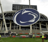 "In this May 15, 2014 file photo, a logo is lifted by crane to the back of a scoreboard at Penn State's Beaver Stadium in State College, Pa.   Judge Gary Glazer is expected to release records Tuesday, July 12, 2016, that also may contain details about claims Penn State assistant coaches saw ""inappropriate contact"" and ""sexual contact"" between Sandusky and a child in 1987 and 1988. AP Photo/Centre Daily Times, Nabil K. Mark."