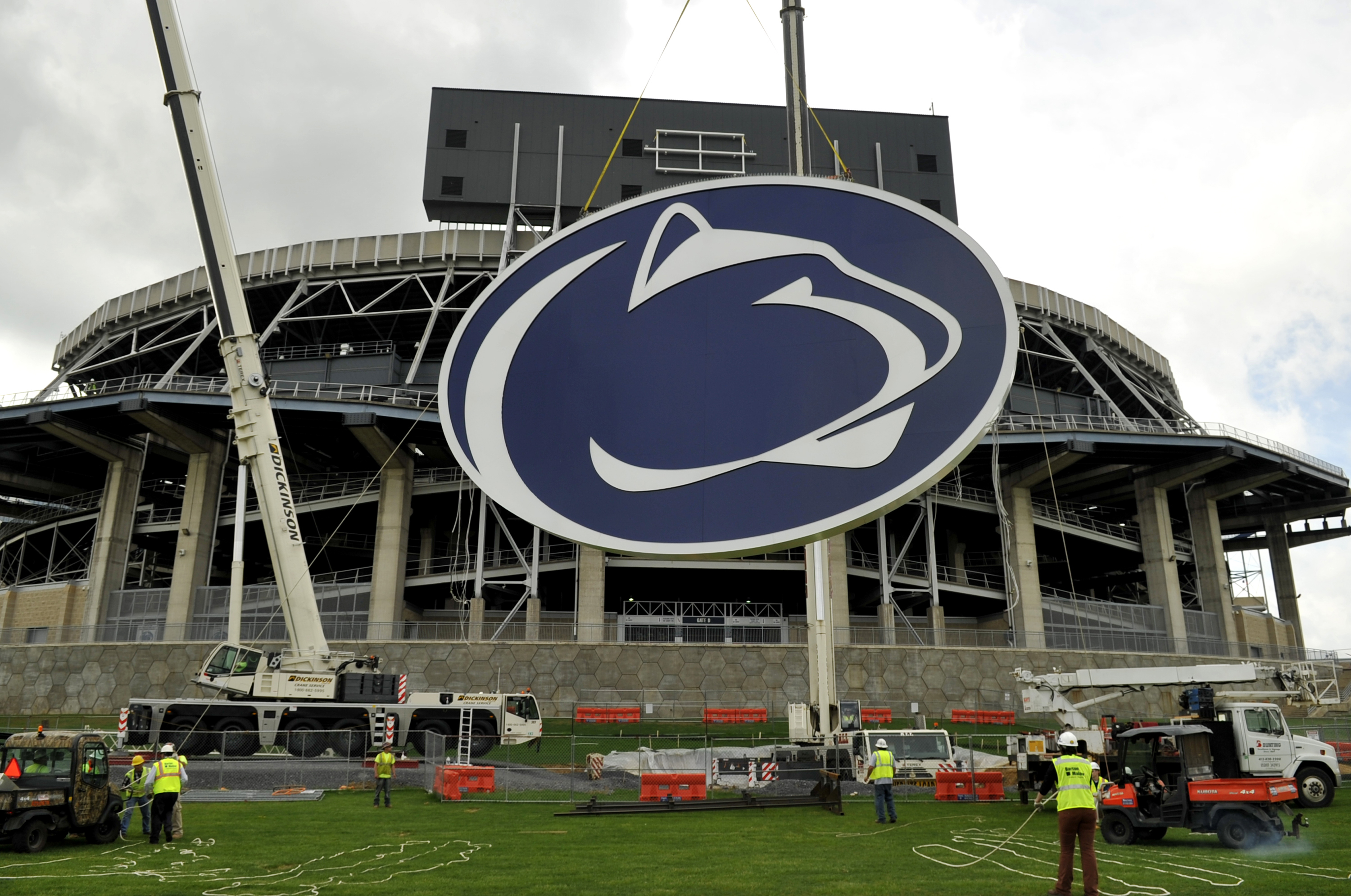 """In this May 15, 2014 file photo, a logo is lifted by crane to the back of a scoreboard at Penn State's Beaver Stadium in State College, Pa.   Judge Gary Glazer is expected to release records Tuesday, July 12, 2016, that also may contain details about claims Penn State assistant coaches saw """"inappropriate contact"""" and """"sexual contact"""" between Sandusky and a child in 1987 and 1988. AP Photo/Centre Daily Times, Nabil K. Mark."""