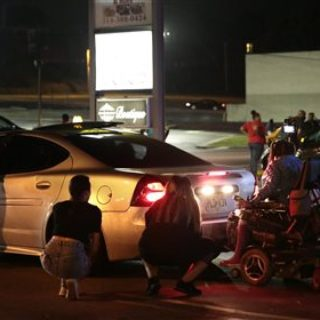 Protesters hide behind cars after shots were fired Tuesday, Aug. 9, 2016, in Ferguson, Mo., during a demonstration on the second anniversary of Michael Brown's death. Witnesses told an Associated Press reporter that a car sped through a group of protesters who were blocking a street during the demonstration marking two years since the unarmed black 18-year-old's fatal shooting by a white police officer. They said the car struck a young man so hard that he flew into the air. As the car drove away, shots were fired, they said.  Photo by Robert Cohen.