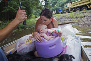 Danielle Blount kisses her 3-month-old baby Ember as she feeds her while they wait to be evacuated by members of the Louisiana Army National Guard near Walker, La., after heavy rains inundating the region, Sunday, Aug. 14, 2016. Photo by Max Becherer, Associated Press.