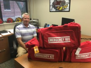 Kirk Turner posed behind the emergency kit bags that were handed out during orientation for building emergency coordinators. Photo by Ashley Ford, Texan News.